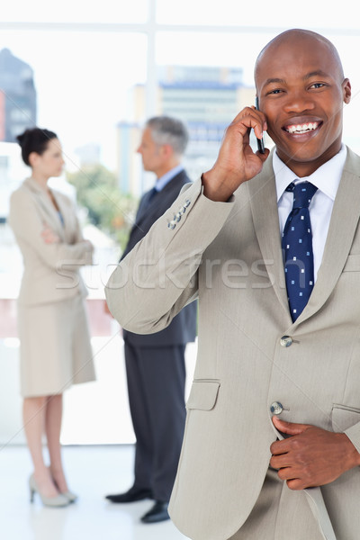 Young manager using a cell phone while unbuttoning his suit jacket Stock photo © wavebreak_media