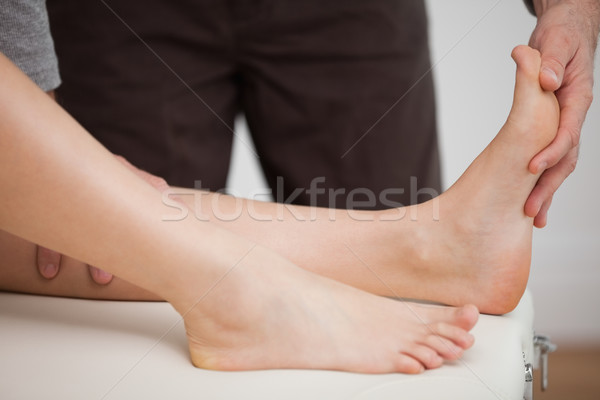 Physiotherapist manipulating the foot of a patient in a room Stock photo © wavebreak_media