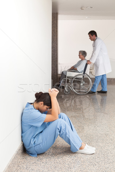 Nurse sitting on the ground in the hallway getting depressed Stock photo © wavebreak_media