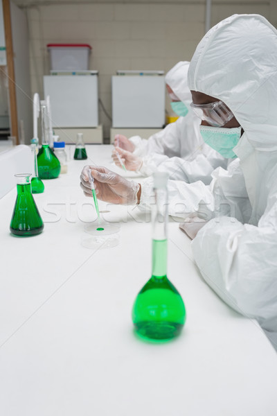 Chemists in protective suits working with green chemical in the lab Stock photo © wavebreak_media