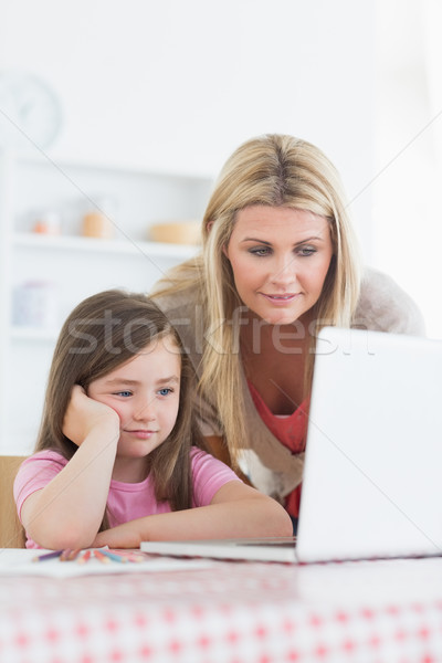 Stock photo: Mother and child looking at laptop on kitchen table