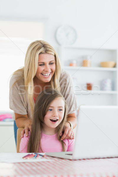 Stock photo: Woman and daughter sitting at the table at the kitchen both smiling at the laptop