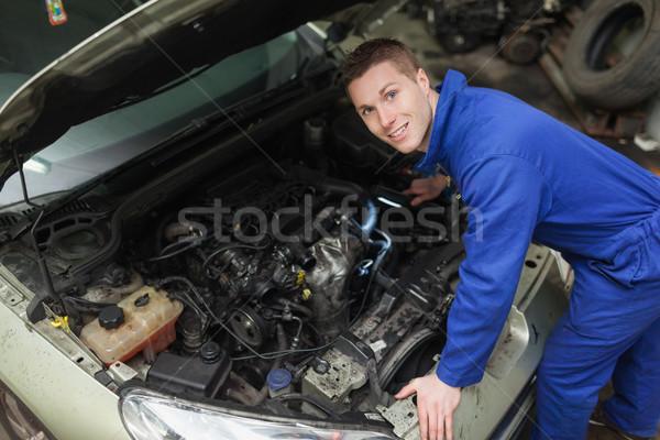 Happy mechanic examining car engine Stock photo © wavebreak_media