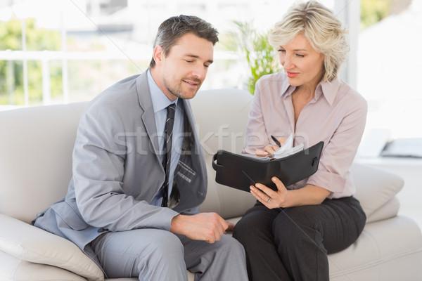 Okos üzletember titkárnő néz napló kanapé Stock fotó © wavebreak_media