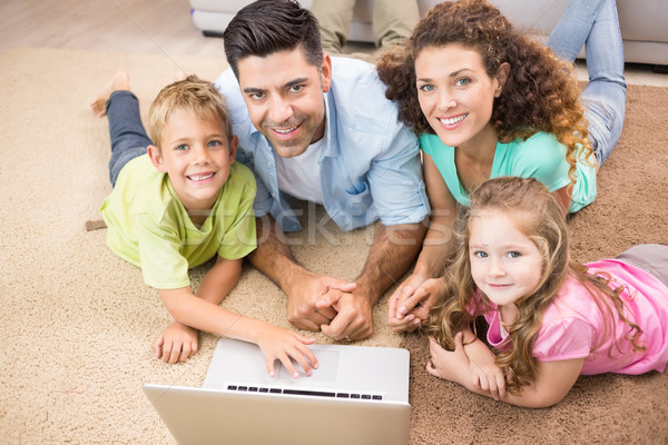 Happy siblings lying on the rug using laptop with their parents Stock photo © wavebreak_media