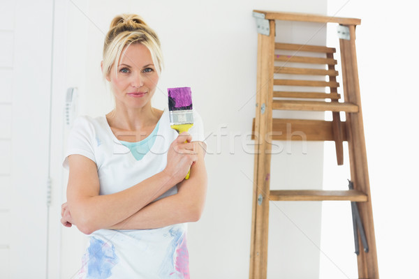 Beautiful woman holding paint brush in new house Stock photo © wavebreak_media