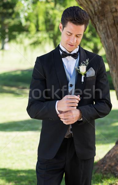 Handsome groom adjusting sleeve in garden Stock photo © wavebreak_media