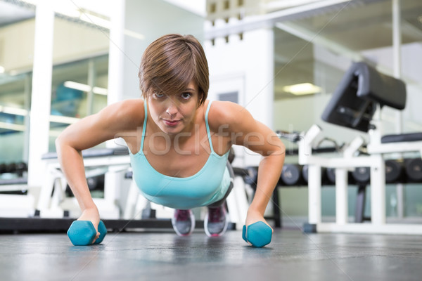 Fit brunette in plank position with dumbbells Stock photo © wavebreak_media
