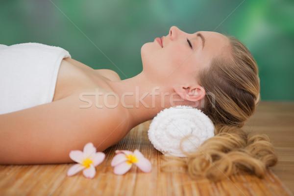 Peaceful blonde lying on bamboo mat with flowers Stock photo © wavebreak_media