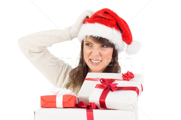 Cute brunette scratching head and holding gifts Stock photo © wavebreak_media