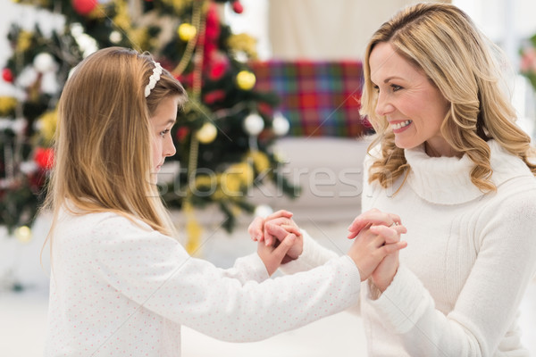 Festive mother and daughter beside christmas tree Stock photo © wavebreak_media