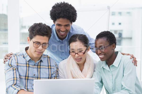 Casual business team having a meeting using laptop Stock photo © wavebreak_media