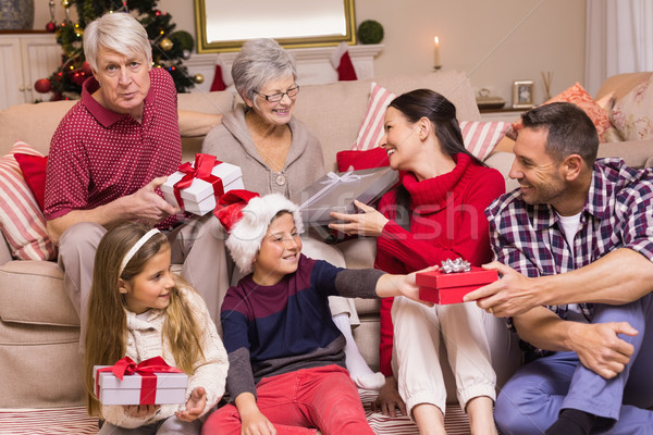 Multi generation family exchanging presents on couch Stock photo © wavebreak_media