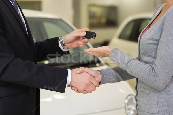 Businessman giving car key while shaking a customer hand Stock photo © wavebreak_media