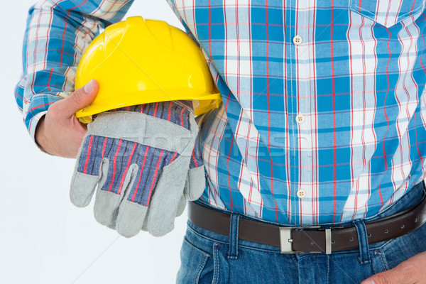 Construction worker holding hard hat and gloves Stock photo © wavebreak_media