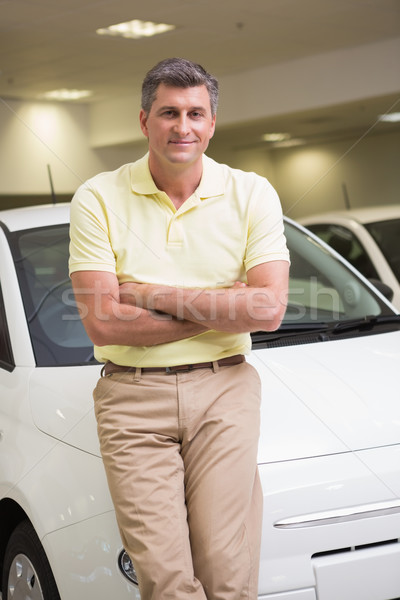 Smiling customer leaning on car with arms crossed Stock photo © wavebreak_media