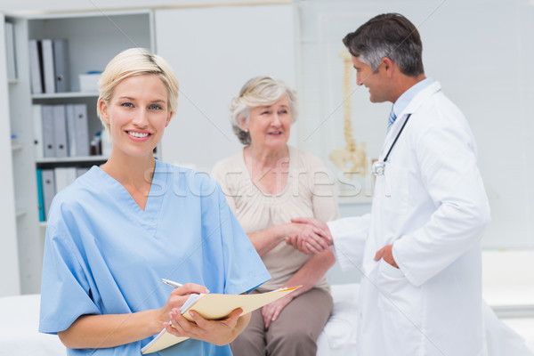 Nurse making reports while doctor and patient shaking hands Stock photo © wavebreak_media