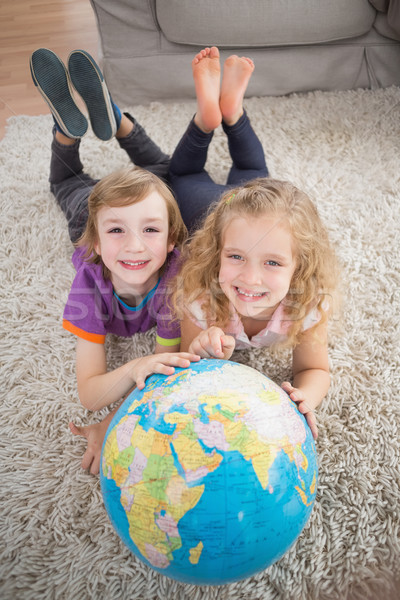 Brother and sister with globe lying on rug Stock photo © wavebreak_media