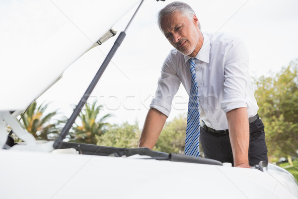 Upset man checking his car engine after breaking down  Stock photo © wavebreak_media