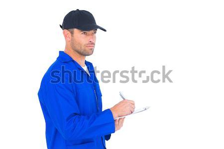 Mechanic in blue overalls writing on clipboard Stock photo © wavebreak_media
