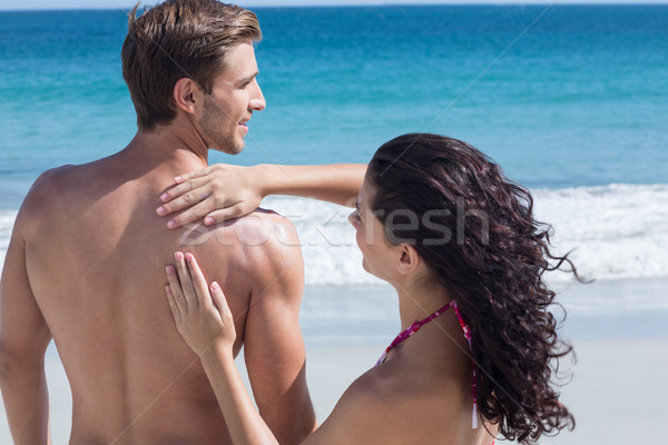 Pretty brunette putting sun tan lotion on her boyfriend Stock photo © wavebreak_media