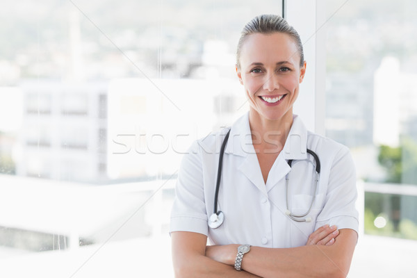 happy doctor smiling at camera with arms crossed Stock photo © wavebreak_media