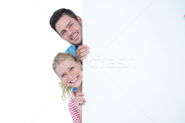 Smiling young couple hiding behind a blank sign Stock photo © wavebreak_media