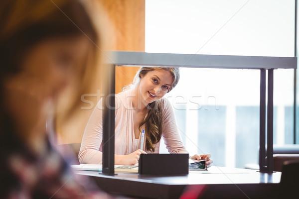 Smiling student sitting next to the window taking notes Stock photo © wavebreak_media