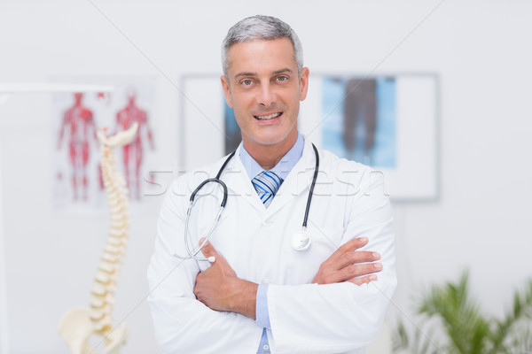 Happy doctor looking at camera with arms crossed  Stock photo © wavebreak_media
