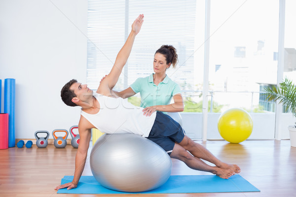 Trainer helping man with exercise ball Stock photo © wavebreak_media
