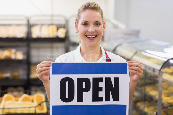 Portrait of a smiling blonde woman holding a sign  Stock photo © wavebreak_media