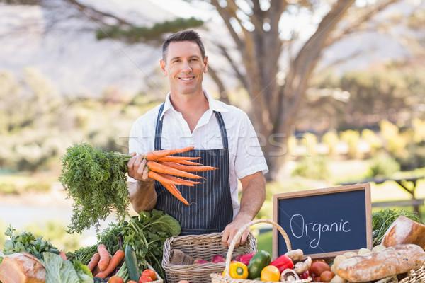 Smiling farmer holding a bunch of carrots Stock photo © wavebreak_media