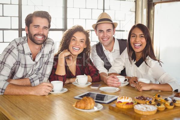 Nevet barátok élvezi kávé csemegék portré Stock fotó © wavebreak_media