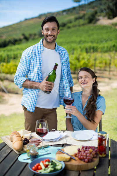 Stock photo: Portrait of happy couple holding red wine bottle and glass