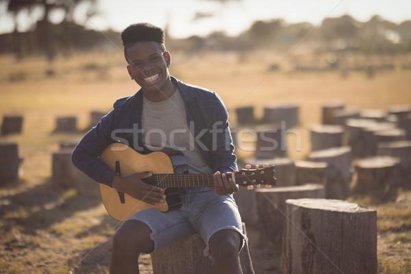 Portret glimlachend jonge man spelen gitaar vergadering Stockfoto © wavebreak_media