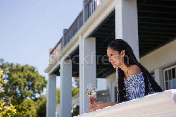 Thoughtful young woman with white wine glass standing in balcony at restaurant Stock photo © wavebreak_media