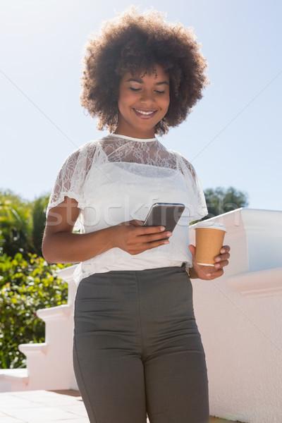 Mujer sonriente teléfono móvil desechable taza cielo Foto stock © wavebreak_media