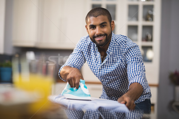 Portrait of smiling young man ironing cloth in kitchen Stock photo © wavebreak_media
