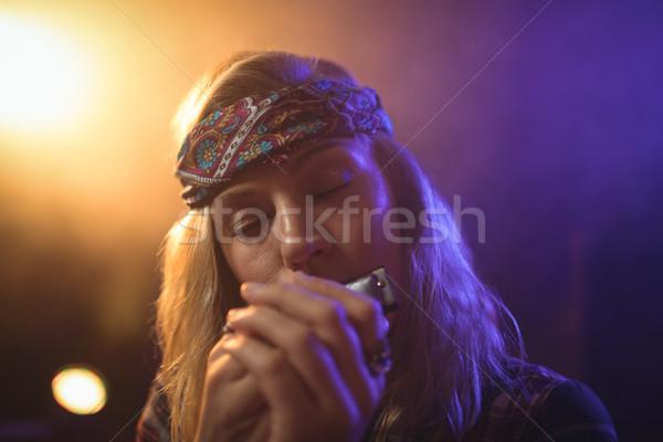 Mooie vrouwelijke muzikant spelen mondharmonica discotheek Stockfoto © wavebreak_media