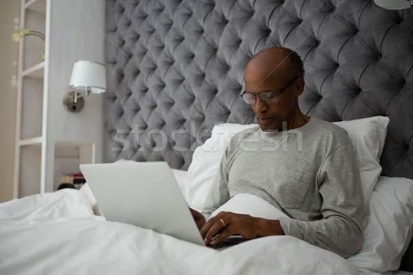 Stock photo: Senior man using laptop while sitting on bed