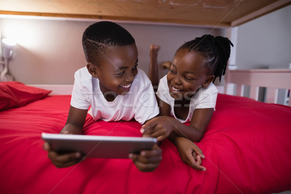 Smiling brother and sister using digital tablet while lying on bed Stock photo © wavebreak_media