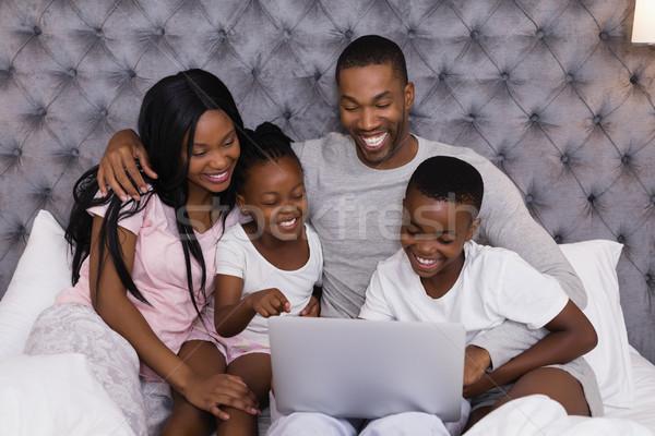 Familia feliz usando la computadora portátil junto cama sesión casa Foto stock © wavebreak_media