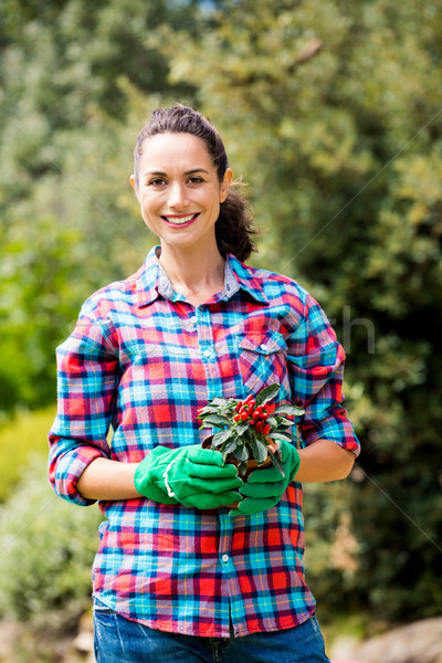 Portrait of woman with potted plant against trees Stock photo © wavebreak_media