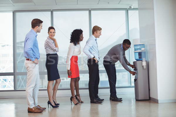 Business people standing by water cooler at office Stock photo © wavebreak_media