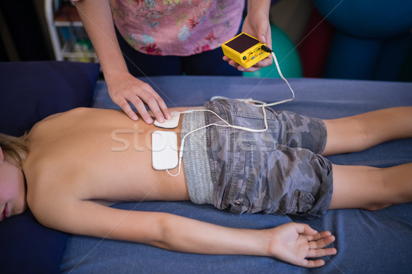 High angle view of female therapist placing electrodes on back Stock photo © wavebreak_media