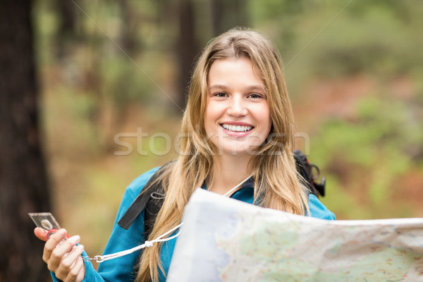 Young pretty hiker using compass and map looking at camera Stock photo © wavebreak_media