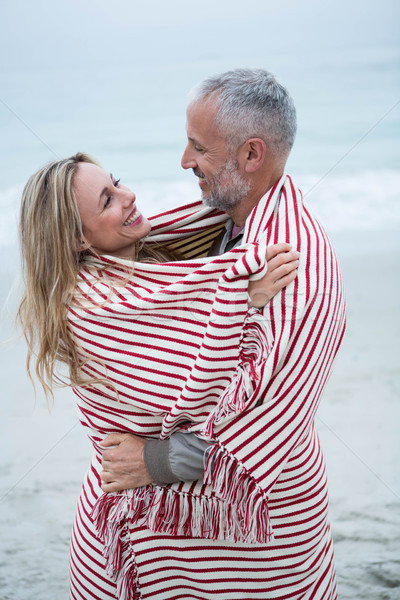 Couple embracing while wrapped in a beach towel Stock photo © wavebreak_media