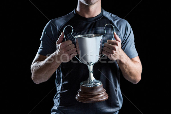 Victorious rugby player holding trophy Stock photo © wavebreak_media