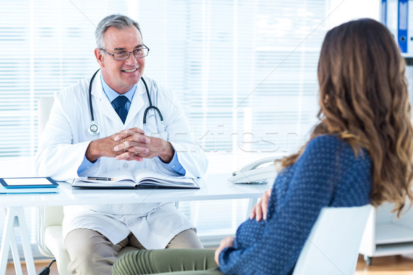 Male doctor discussing with pregnant woman in clinic Stock photo © wavebreak_media