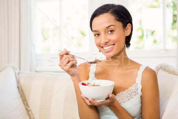 привлекательный брюнетка еды злаки диван счастливым Сток-фото © wavebreak_media